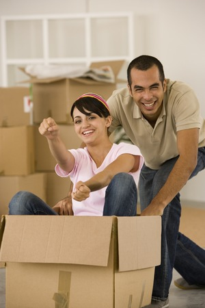 Man pushing wife in moving box 스톡 콘텐츠