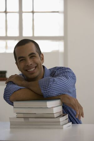 handsfree: Young man leaning on books