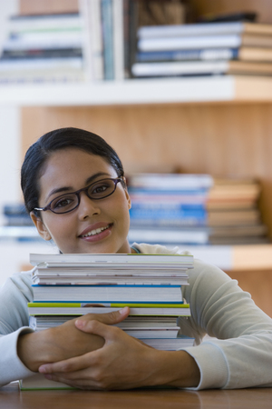 spectating: Young woman with stack of books