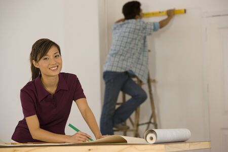 scaling ladder: Asian couple hanging wall paper LANG_EVOIMAGES