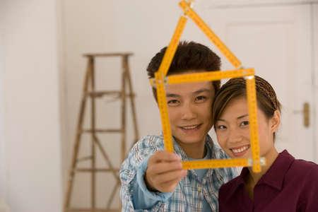 scaling ladder: Asian couple with folding ruler shaped like house