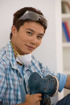 casualness: Asian man holding power sander