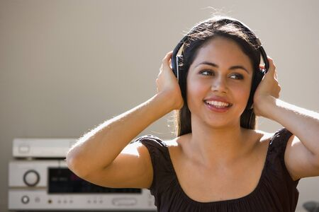 casualness: Young woman listening to headphones LANG_EVOIMAGES