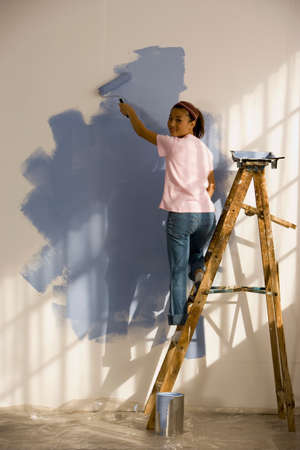 front raise: Asian woman painting interior of house LANG_EVOIMAGES