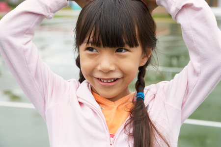 gratifying: Asian girl with hands on head LANG_EVOIMAGES