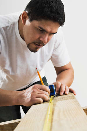bathtowel: Hispanic man using tape measure on wood board LANG_EVOIMAGES