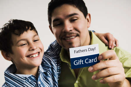 fathering: Hispanic father and son with Father's Day gift card