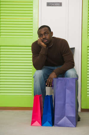 shopping buddies: African man waiting outside dressing rooms LANG_EVOIMAGES