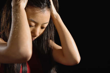 attired: Sweaty Asian woman with hands in hair