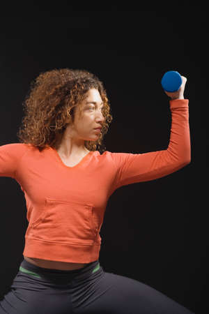 saturating: Mixed Race woman holding dumbbell