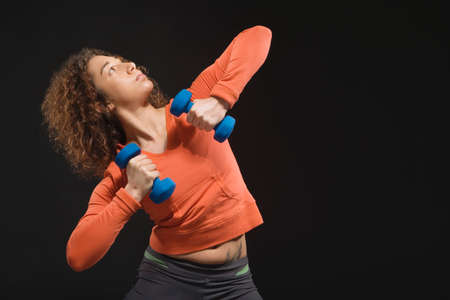 squatter: Mixed Race woman holding dumbbells LANG_EVOIMAGES