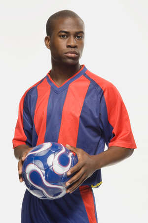 coordinating: African American male soccer player holding ball LANG_EVOIMAGES
