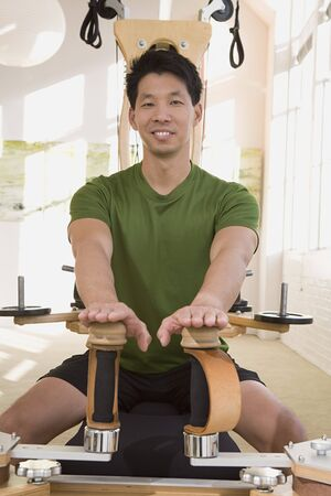 holistic view: Asian man stretching on exercise equipment LANG_EVOIMAGES