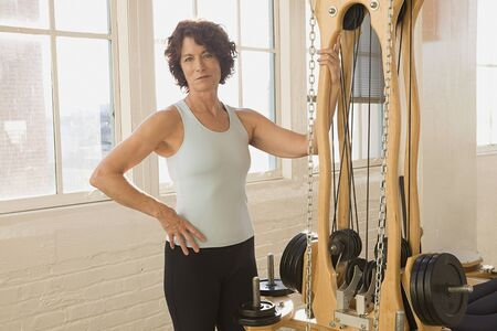 holistic view: Senior woman standing next to exercise equipment