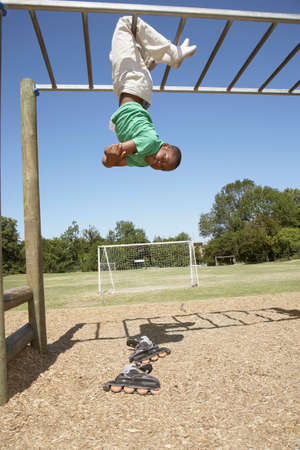 jungle gym: African boy hanging from jungle gym LANG_EVOIMAGES