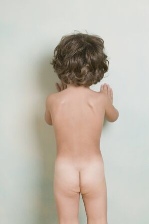 concentrates: Rear view of nude Hispanic boy