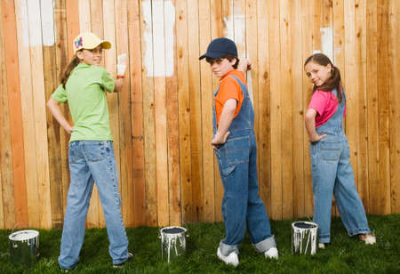 cooperating: Mixed Race children painting fence