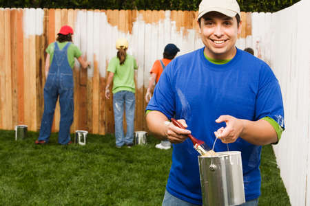 hispanic woman: Mixed Race family painting fence
