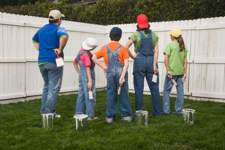 children painting: Mixed Race family painting fence
