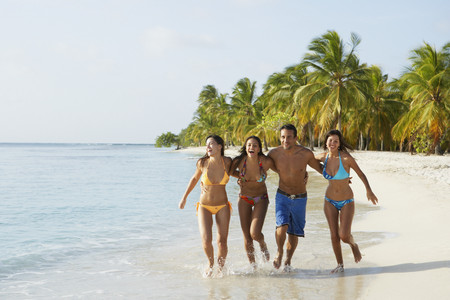 ビーチで実行している南アメリカの友人 写真素材