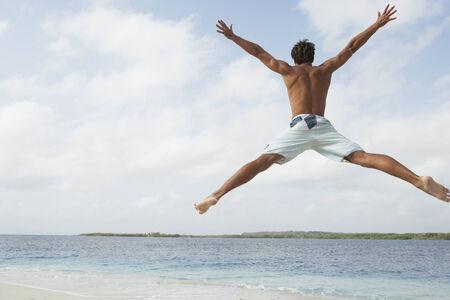 South American man jumping on beach Stok Fotoğraf