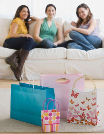 Three young women looking at gift bags Imagens - 35735345