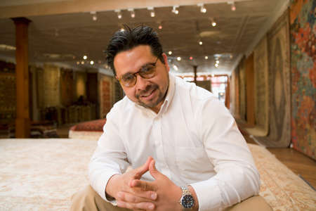Hispanic business owner in rug shop