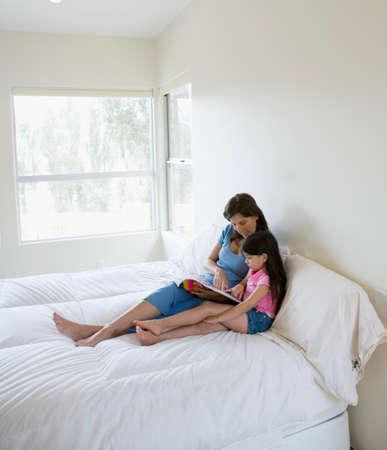 interrogating: Hispanic mother reading to daughter