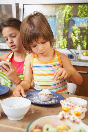 decorating: Hispanic sisters decorating cupcakes LANG_EVOIMAGES