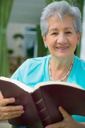 bare waist: Senior Hispanic woman reading book