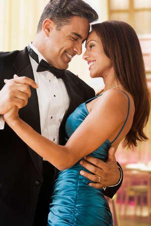 eveningwear: Hispanic couple dancing in eveningwear LANG_EVOIMAGES