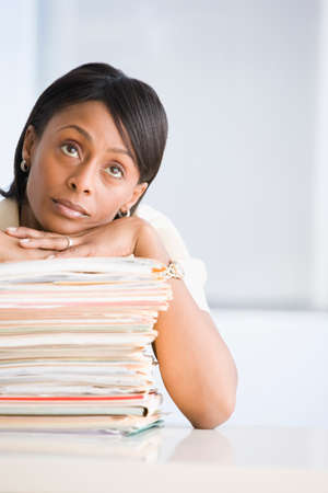 mathematician: African American businesswoman leaning on stack of paperwork