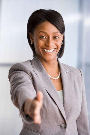 one mid adult woman only: African American businesswoman extending hand to shake