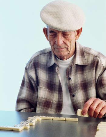 80 plus adult: Senior Hispanic man playing dominoes