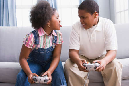 chinese american ethnicity: African American sister and brother playing video games LANG_EVOIMAGES