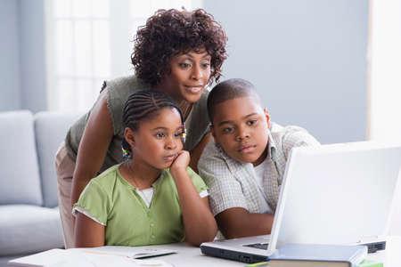deberes: Madre afroamericana ayudar a los ni�os con la tarea