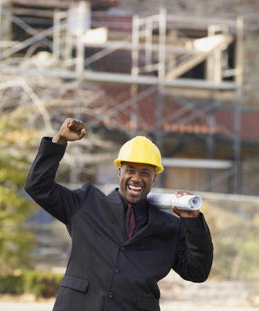 misbehaving: African American businessman cheering with blueprints LANG_EVOIMAGES