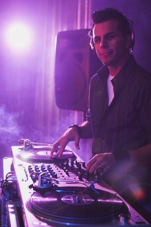 new age music: Hispanic dj playing at nightclub LANG_EVOIMAGES