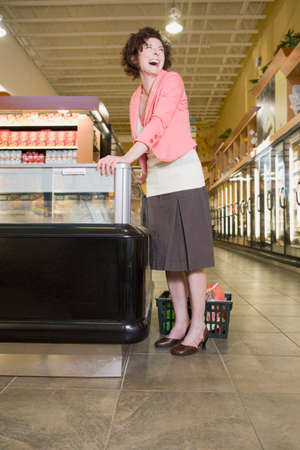tugging: Woman laughing in grocery store LANG_EVOIMAGES