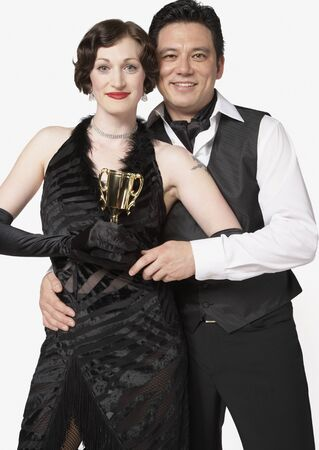 only one mid adult man: Multi-ethnic couple holding tango trophy LANG_EVOIMAGES