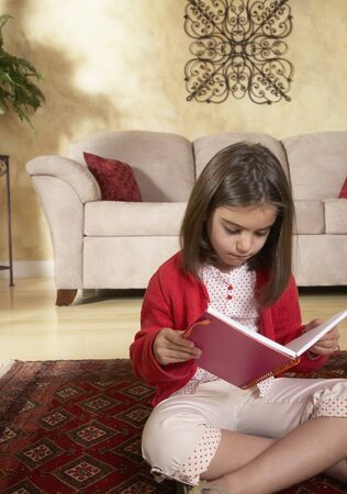 Middle Eastern girl reading on floor