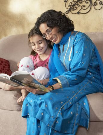 living being: Indian grandmother reading to granddaughter LANG_EVOIMAGES