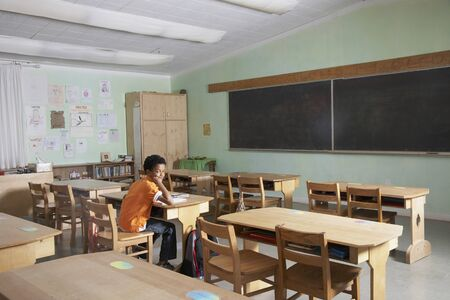 loitering: Mixed Race boy in empty classroom