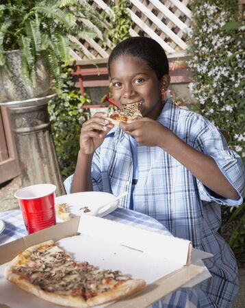 African boy eating pizza