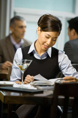 connexion: Asian woman reading at restaurant