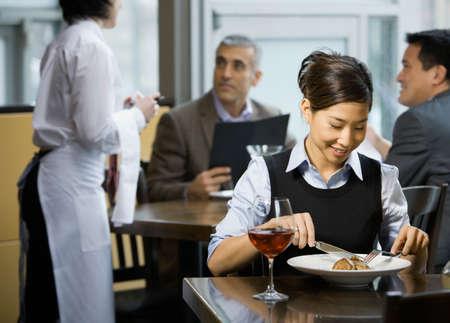Asian woman eating at restaurant