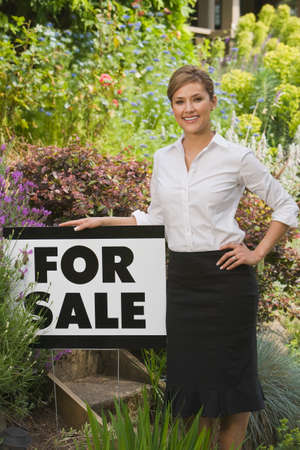 milepost: Hispanic woman next to For Sale sign LANG_EVOIMAGES