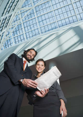 intriguing: Hispanic businesspeople holding newspaper LANG_EVOIMAGES