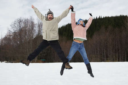 pacific islander ethnicity: Mixed Race couple jumping in snow