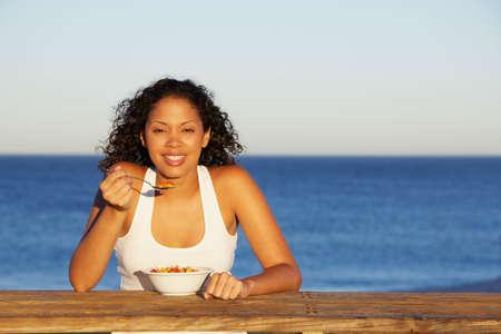 comiendo cereal: Mujer de la raza mezclada comer cereales LANG_EVOIMAGES